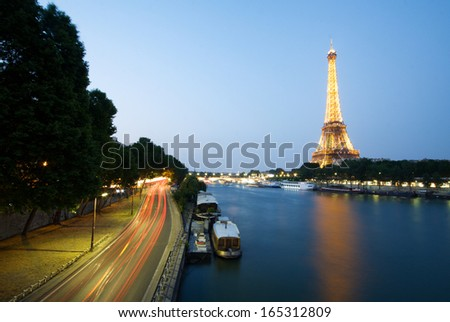 PARIS - JULY 9: Eiffel Tower brightly illuminated at dusk on July 9, 2013 in Paris. Erected in 1889 as the entrance arch to the 1889 World's Fair, it has become a global cultural icon of France. - stock photo