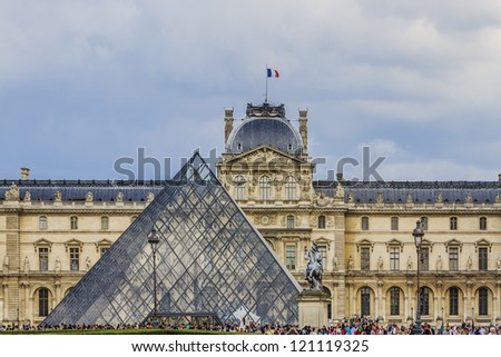 PARIS - JULY 24: Louvre building and Pyramid on July 24, 2012 in Louvre Museum, Paris, France. With 8.8 million annual visitors, Louvre is consistently the most visited museum worldwide. - stock photo