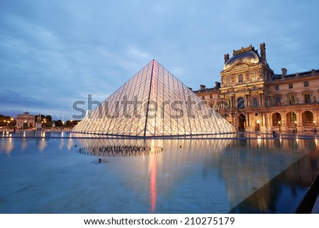 PARIS - JULY 7: Louvre museum and pyramid night view on July 7th, 2014 in Paris, France. Louvre museum hosts one of the biggest art collection in the world. - stock photo