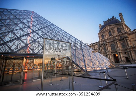 Paris - July 6: Louvre museum at dusk on July 6, 2015 in Paris. This is one of the most popular tourist destinations in France displayed over 60,000 square meters of exhibition space - stock photo