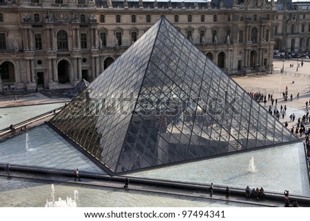 PARIS - JULY 22: Louvre pyramid on July 22, 2011 in Louvre Museum, Paris, France. With 8.5m annual visitors, Louvre is consistently the most visited museum worldwide. - stock photo