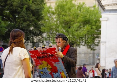 PARIS -  1 JULY 2014: Painter and his model on Montmartre hill on 1 JULY 2014 in Paris, France. Many artists worked of Montmartre such as Pablo Picasso or Vincent van Gogh  - stock photo