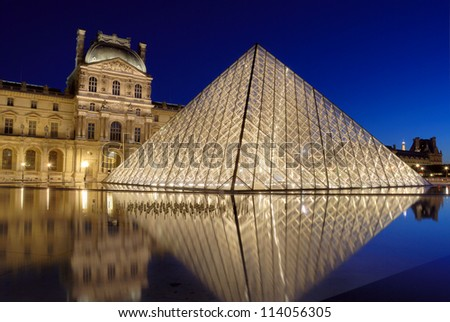 PARIS - JULY 30: Pyramid near to Louvre on July 30, 2012 in Paris, France. Illumination project was developed by Claude Engl who has established halogen lamps on internal perimeter of a pyramid. - stock photo