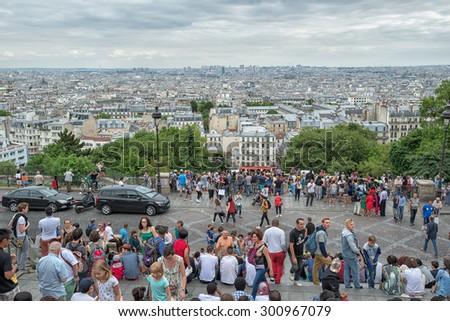 PARIS - JULY 20: tourists at the Montmartre viewpoint on July 20, 2015 in Paris, France. In year 2014 more than 15 million people visited Paris.     - stock photo