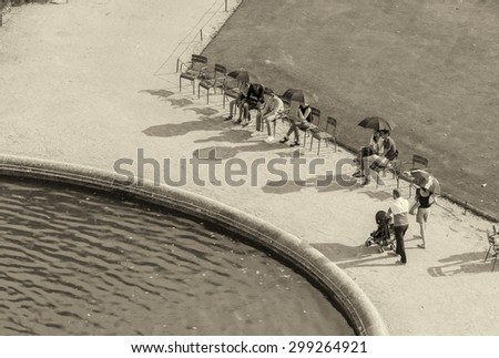 PARIS - JULY 20, 2014: Tourists enjoy a beautiful summer day along Tuileries Gardens. The city attracts more than 30 million people annually.