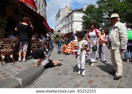 PARIS - JULY 22: Tourists in Montmartre district on July 22, 2011 in Paris, France. Monmartre area is popular among tourists in Paris, the most visited city worldwide. - stock photo
