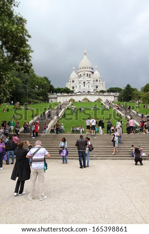 PARIS - JULY 22: Tourists stroll in Montmartre district on July 22, 2011 in Paris, France. Paris is the most visited city in the world with 15.6 million international arrivals in 2011.  - stock photo