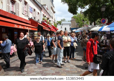PARIS - JULY 22: Tourists visit Montmartre district on July 22, 2011 in Paris, France. Paris is the most visited city in the world with 15.6 million international arrivals in 2011. - stock photo