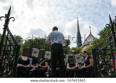 PARIS - JULY 6: Unidentified musicians play classical music in park near Notre Dame church on July 6, 2013 in Paris, France. In summer Paris offers a variety of entertainment to citizens and tourists. - stock photo