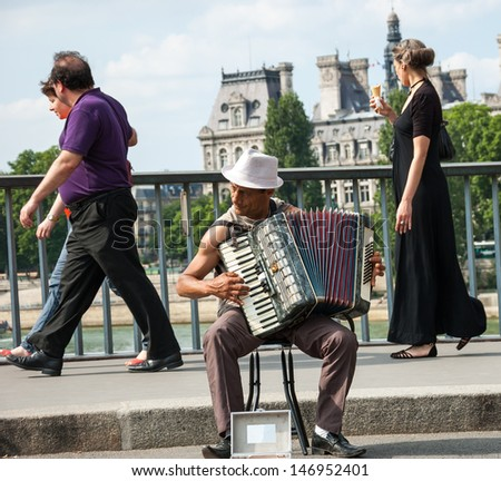 PARIS - JULY 6: Unidentified senior musician play accordion on the bridge near  Hotel de Ville and the tourists passing by on July 6, 2013 in Paris, France. Dozens buskers perform on streets of Paris. - stock photo