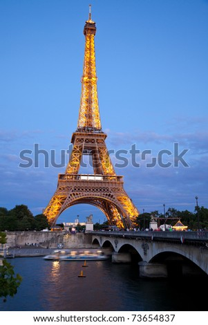 PARIS - JULY 24: Vertical panoramic of The Eiffel Tower illuminated at dusk July 24, 2009 in Paris, France. The Eiffel tower is the tallest monument in Paris and one of the most visited in the World - stock photo