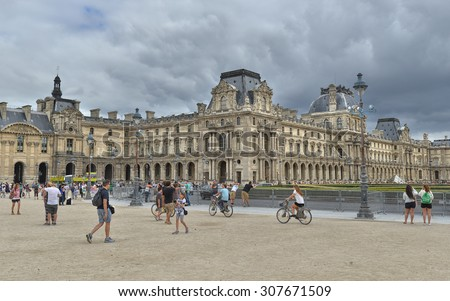 PARIS - JULY 21: view of the Louvre Museum on cloudy day on July 21, 2015 in Paris, France. In year 2014 more than 15 million tourists visited the city of Paris. - stock photo