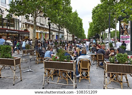 PARIS, JUN 22:Crowded terrace on the Avenue des Champs-elysees during a cloudy afternoon on 22 June 2010. Avenue des Champs Elysees is the biggest and most famous and expensive boulevard in the world. - stock photo