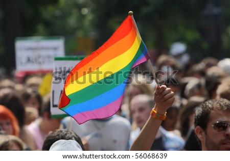 PARIS - JUNE 26: A person waves with the rainbow flag to support gay rights during the Paris Gay Pride parade, on June 26, 2010 in Paris, France. - stock photo