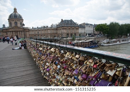 PARIS - JUNE 27: Couples have attached padlocks with their names on them to the Pont des Arts bridge, then throwing the key into the Seine river below, as a romantic gesture, June 27, 2013. - stock photo