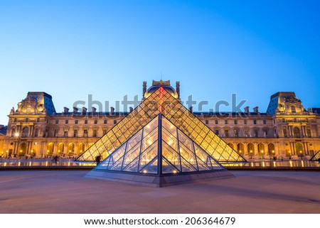 Paris - June 18: Louvre museum at dusk on June 18, 2014 in Paris. This is one of the most popular tourist destinations in France displayed over 60,000 square meters of exhibition space..  - stock photo