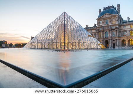 Paris - June 18: Louvre museum at dusk on June 18, 2014 in Paris. This is one of the most popular tourist destinations in France displayed over 60,000 square meters of exhibition space  - stock photo