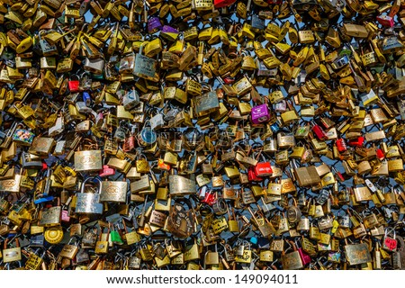 PARIS - JUNE 30: Love Padlocks at Pont des Arts on June 30, 2013, in Paris. The thousands of locks of loving couples symbolize love forever. - stock photo