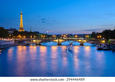 PARIS - JUNE 14: Night view of Eiffel Tower and Pont des invalides on June 14, 2015 in Paris. The Eiffel tower located on the Champ de Mars in Paris is the most famous landmark of France. - stock photo
