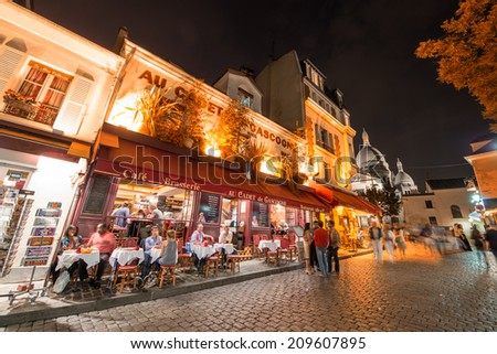 PARIS - JUNE 23, 2014: Tourists and locals walk in Montmartre streets at night. Montmartre attracted many famous modern painters in the early 20th century - stock photo
