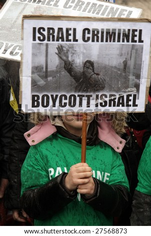 PARIS - MARCH 28: A child holds a poster during the Anti-Israeli manifestation on March 28, 2009 at Place du Chatelet in Paris, France. The poster says 'Israel is criminal. Boycott Israel' - stock photo