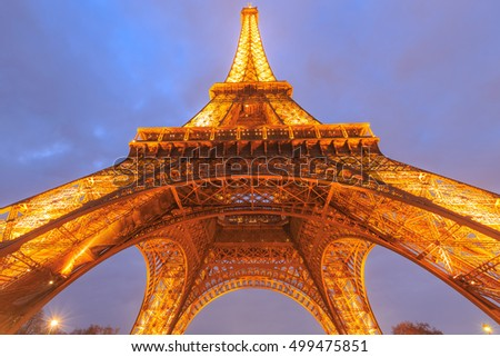 PARIS - MARCH 14: Eiffel Tower brightly illuminated at dusk on Mar 14, 2015 in Paris. The Eiffel tower is the most visited monument of France.