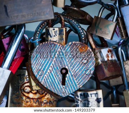 PARIS - MARCH 24: Heart shaped vintage love lock with stripes as seen on March 24, 2013 in Paris, France. Ritual of affixing padlocks, as symbol of love, to bridge is spread in Europe from 2000s. - stock photo