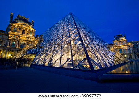 PARIS - MARCH 26: Louvre Pyramid shines at dusk on March 26, 2010 in Paris. Louvre is the biggest Museum in Paris displaying over 60,000 square meters of exhibition space. - stock photo