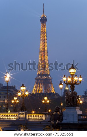 PARIS - MARCH 28: Night illumination on the bridge of Alexander III and the Eiffel Tower on March 28, 2011 in Paris. This illumination admire 25,000,000 tourists a year. - stock photo