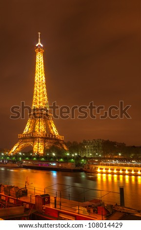 PARIS- MARCH 31: Night image in Paris of the illuminated Eifel Tower, river Seine and a wooden ship  on March 31, 2012 in Paris,France.Eiffel Tower is the most popular French touristic attraction. - stock photo