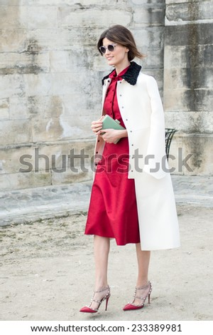 PARIS - MARCH 5, 2013: Stylish European woman with red skirt and white trench coat in the Tuileries Garden. Paris Fashion Week: Ready to Wear 2014/2015 is held from February 26 to March 6, 2013. - stock photo