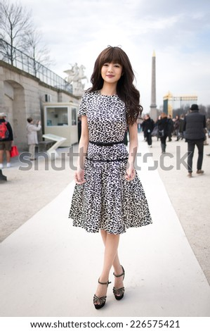 PARIS - MARS 5, 2013: Stylish Asian woman with dalmatian spots skirt in the Tuileries Garden. Paris Fashion Week: Ready to Wear 2013/2014 is held from February 26 to March 6, 2013.