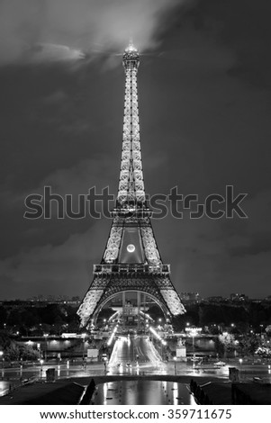 PARIS - MAY 28, 2014: Black and white picture of the Eiffel tower, the most visited and recognized landmark in Paris. The illuminated tower at night is an added attraction. - stock photo
