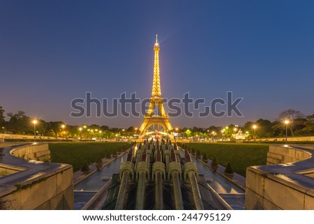 PARIS - MAY 16: Eiffel Tower brightly illuminated at dusk on May 16, 2014 in Paris. The Eiffel tower is the most visited monument of France.