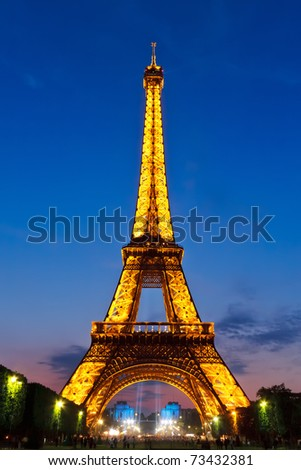 PARIS - MAY 28: Eiffel Tower brightly illuminated at dusk on May 28, 2008 in Paris. The Eiffel tower is is the tallest monument in Paris and the most-visited in France. - stock photo