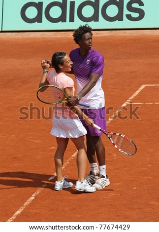 PARIS - MAY 21: Gael Monfils of France and Francesca Schiavone of Italy dance during the exhibition match at French Open, Roland Garros on May 21, 2011 in Paris, France. - stock photo