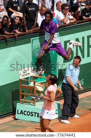 PARIS - MAY 21: Gael Monfils of France and Francesca Schiavone of Italy play the exhibition match at French Open, Roland Garros on May 21, 2011 in Paris, France. - stock photo