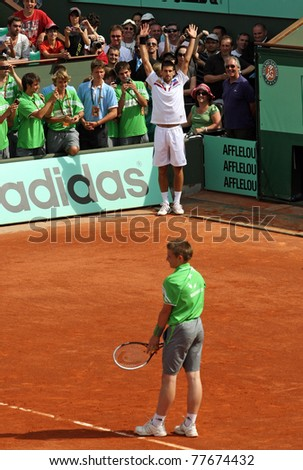 PARIS - MAY 21: Novak Djokovic of Serbia exchanges places with a ball boy during the exhibition match  at French Open, Roland Garros on May 21, 2011 in Paris, France. - stock photo
