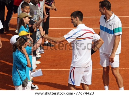 PARIS - MAY 21: Novak Djokovic of Serbia greets children after the exhibition match  at French Open, Roland Garros on May 21, 2011 in Paris, France. - stock photo