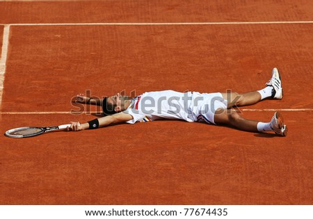 PARIS - MAY 21: Novak Djokovic of Serbia lies down at the centre court during the exhibition match  at French Open, Roland Garros on May 21, 2011 in Paris, France. - stock photo