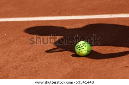 PARIS - MAY 20: Official ball of the French Open Grand Slam tennis tournament with the shadow of a tennis player on the clay clourt of Roland Garros on May 20, 2010 in Paris, France. - stock photo