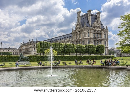 PARIS - MAY 14, 2014: Parisians and tourists in famous Tuileries garden. Tuileries Garden (Jardin des Tuileries) is a public garden located between the Louvre Museum and Place de la Concorde. France. - stock photo