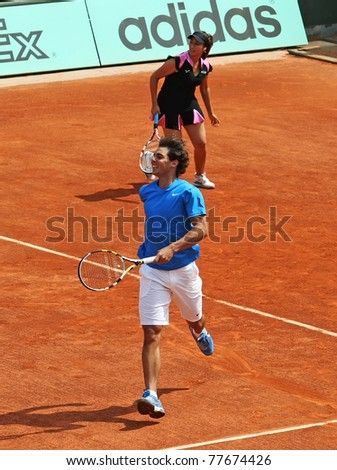 PARIS - MAY 21: Rafael Nadal of Spain and Aravane Rezai (FRA) play the exhibition match  at French Open, Roland Garros on May 21, 2011 in Paris, France. - stock photo