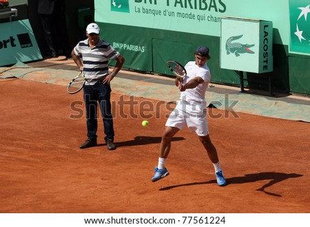 PARIS - MAY 19: Rafael Nadal of Spain practices as his coach Tony Nadal watches at Court Suzanne Lenglen at French Open, Roland Garros on May 19, 2011 in Paris, France. - stock photo