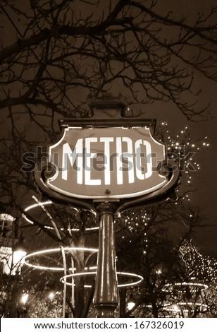 Paris Metro subway sign and Christmas illumination. Sepia. - stock photo