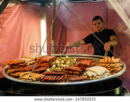 PARIS - NOV 30: Unidentified young man cook an assortment of grilled sausages and kebabs on big hanging grill at Christmas market  on November 30, 2013 in Paris, France. - stock photo
