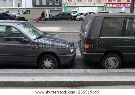 PARIS - OCTOBER 12, 2014: Close parked cars in de streets of Paris. At many insurance companies in France bumpers are not insured  - stock photo