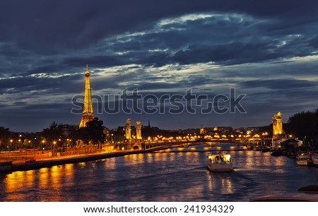 PARIS - OCTOBER 1,2012: Eiffel Tower and Pont Alexandre III at night  in Paris. The Eiffel tower is the most visited monument of France with about 6 million visitors every year.  - stock photo