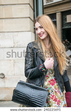 PARIS - OCTOBER 2, 2013: Stylish woman during the Paris Fashion Week on October 2, 2013 in Paris, France. Paris Fashion Week is a clothing trade show held semi-annually each year in Paris, France. - stock photo