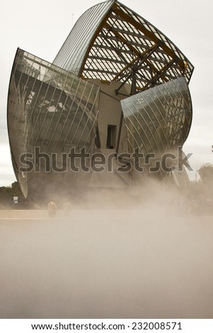 PARIS-OCTOBER 24: The Louis Vuitton Foundation building by the American architect, Frank Gehry seems suspended above the mist from a fountain. It recently opened to the public on October 24 in Paris - stock photo